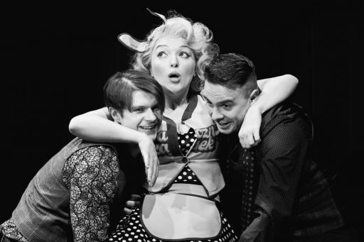 Czarno-białe zdjęcie. Młoda blondynka podtrzymywana jest z dwóch stron przez dwóch młodych mężczyzn.