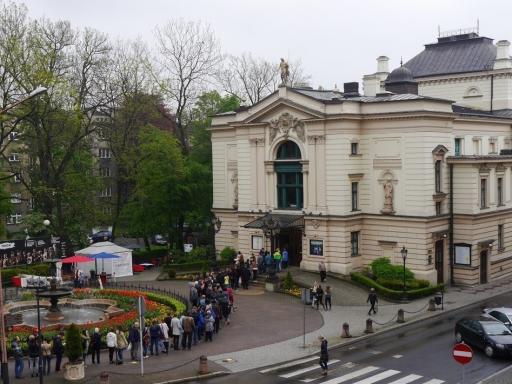 Długa kolejka do kasy teatru przed budynkiem