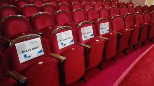 Fotele na teatralnej widowni, na nich przypięte kartki z napisem