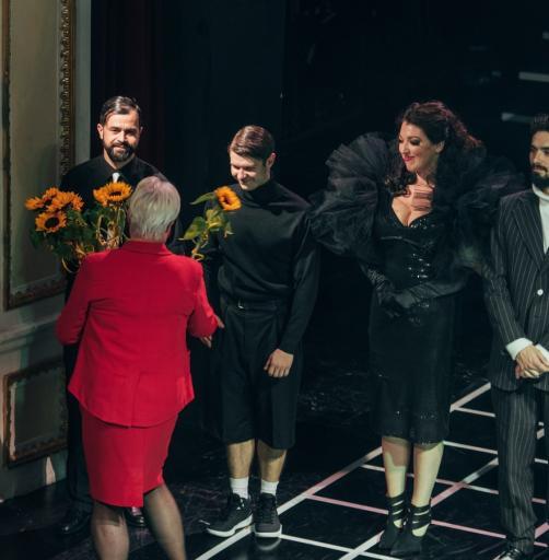 Trzech aktorów i jedna aktorka stoją na scenie z bukietami kwiatów.