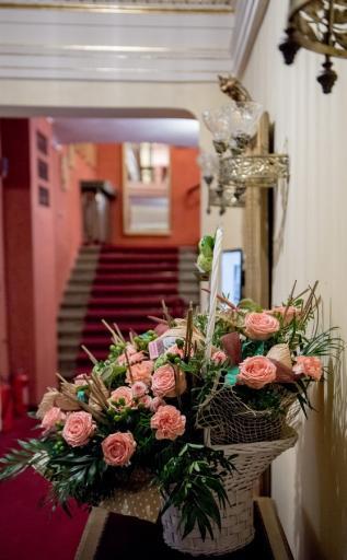 Na zdjęciu fragment stylowego foyer teatru. Na pierwszym planie kosz różowych kwiatów, w tle schody z czerwonym dywanem i fragment białych ścian ozdobionych złoceniami.