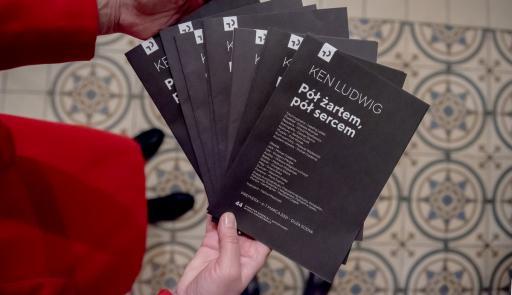 Na zdjęciu ręce osoby, która trzyma kilka programów teatralnych spektaklu