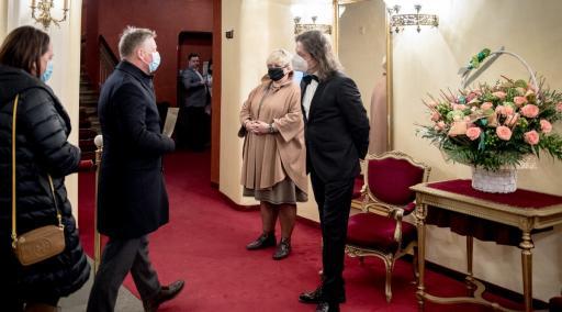 W pobliżu wejścia, w foyer teatru dyrektor wita gości premierowych. Wszyscy w maseczkach ochronnych na twarzach. Na stylowym, czerwono-złotym stoliku stoi duży kosz różowych kwiatów.