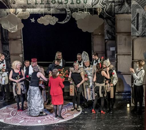 Na zdjęciu scena, na której stoi scenografia spektaklu. Na scenie kilkanaście osób - aktorzy, twórcy, bileterka, która rozdaje artystom kwiaty. Artyści kłaniają się i wymieniają uściski.