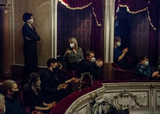 Zdjęcie z fragmentem balkonu i loży teatralnej. W loży siedzą widzowie w maseczkach ochronnych, którzy klaszczą.