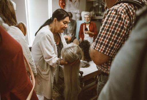 Na zdjęciu pracownia perukarska Teatru Polskiego. Pracowniczka perukarni - brunetka w starszym wieku - podaje osobom niewidomych peruki teatralne do poznawania dotykowego.