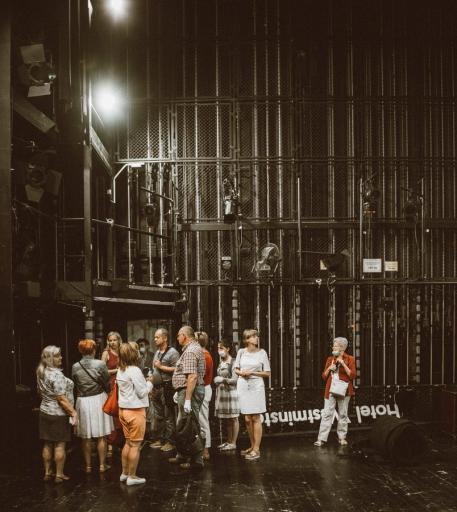 Na zdjęciu fragment kulis, sceny i urządzeń scenicznych. Na scenie stoi grupa osób niewidomych z przewodnikami.