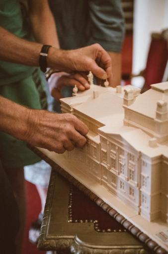 Na zdjęciu makieta budynku Teatru Polskiego i ręce, które dotykowo poznają kształt makiety.