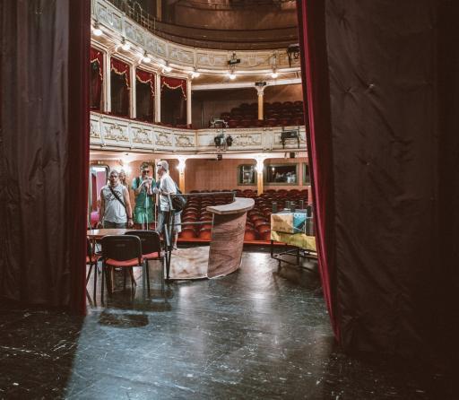 Na zdjęciu fragment sceny i widowni Teatru Polskiego. Na scenie stoją trzy osoby, które zwiedzają teatr.