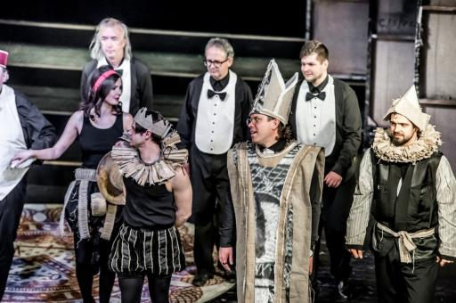 Jedna aktorka i sześciu aktorów w kostiumach teatralnych stoją na scenie po spektaklu, gotowi do ukłonów.