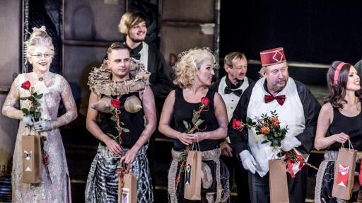 Na scenie, po skończonym spektaklu stoją aktorzy - trzy kobiety i czterech mężczyzn w różnym wieku. Wszyscy uśmiechnięci, ubrani w teatralne kostiumy, w dłoniach trzymają czerwone róże.