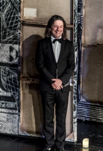 Na scenie, na tle dekoracji stoi uśmiechnięty dyrektor teatru - około sześćdziesięcioletni brunet, z włosami do ramion, ubrany w czarny garnitur, białą koszulę i muszkę.
