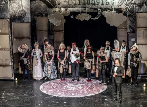 Na scenie scenografia spektaklu z tekturowymi chmurami i księżycem. W dekoracjach stoją aktorzy przygotowani do ukłonów po spektaklu. Wśród nich są trzy kobiety i jedenastu mężczyzn w różnym wieku. Wszyscy trzymają czerwone róże. Nieco przed nimi stoi dyrektor teatru - około sześćdziesięcioletni brunet, w garniturze, białej koszuli i muszce.