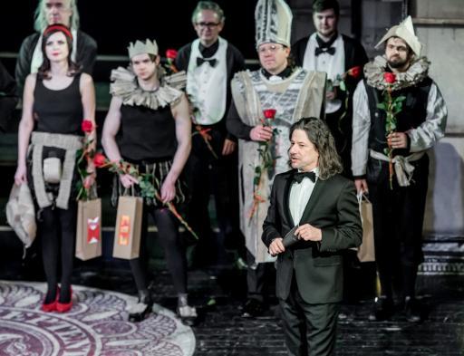 Jedna aktorka, sześciu aktorów i dyrektor teatru stoją na scenie z różami w dłoniach.