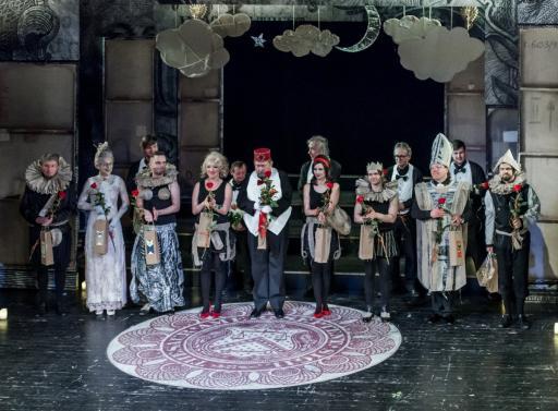 Trzynastu aktorów stoi na scenie, w dekoracjach spektaklu. Wszyscy ubrani są w kostiumy teatralne, z różami w dłoniach, gotowi do ukłonów.