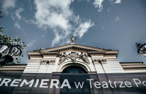 Górny fragment fasady Teatru Polskiego i baner z napisem PREMIERA w Teatrze.