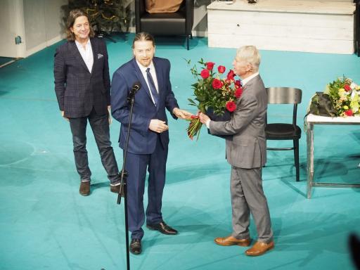 Na scenie stoją: na pierwszym planie aktor Aleksander Pestyk, przyjmuje bukiet kwiatów z rąk Naczelnika Wydziału Kultury Urzędu Miejskiego Przemysława Smyczka. Na drugim planie dyrektor teatru Witold Mazurkiewicz.