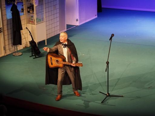 Aktor Aleksander Pestyk stoi na scenie, z gitarą w dłoniach