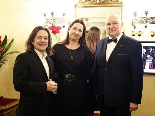 Dyrektor i goście premierowi uśmiechają się i pozują do zdjęcia w foyer teatru