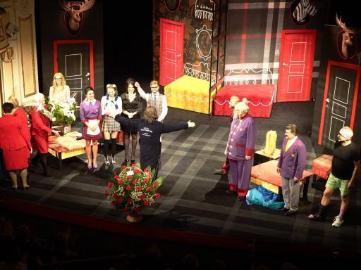 Aktorzy i reżyser stoją na scenie z kwiatami po spektaklu premierowym