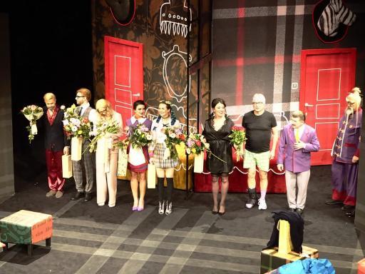 Aktorzy stoją na scenie z kwiatami po spektaklu premierowym