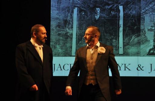 Dwóch mężczyzn w kostiumach z 19 wieku stoi na scenie, na tle grafiki z napisem: Jacek Proszyk & Jacek Kachel