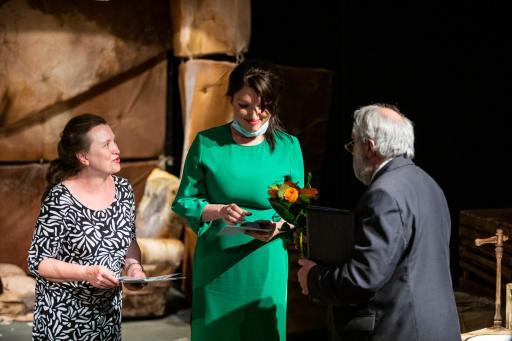 Na zdjęciu na scenie stoją trzy osoby - dwie kobiety (młodsza i starsza) i siwy mężczyzna w garniturze odwrócony tyłem do aparatu.