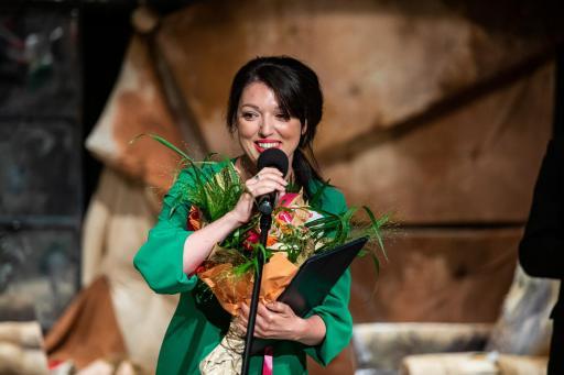 Na zdjęciu uśmiechnięta aktorka Wiktoria Węgrzyn-Lichosyt z bukietem kwiatów w dłoni. Stoi na scenie i mówi do mikrofonu.