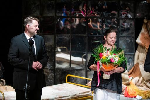 Na zdjęciu, w dekoracjach spektaklu stoi prezydent miasta Jarosław Klimaszewski, obok stoi Halinie Mieszczak z bukietem kwiatów.