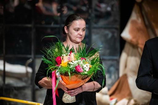 Na zdjęciu na scenie stoi inspicjentka Halina Mieszczak z bukietem kolorowych kwiatów.