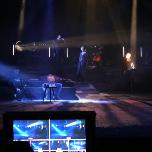 Na pierwszym planie monitor komputera, dalej - kilku aktorów stoi w półmroku sceny.