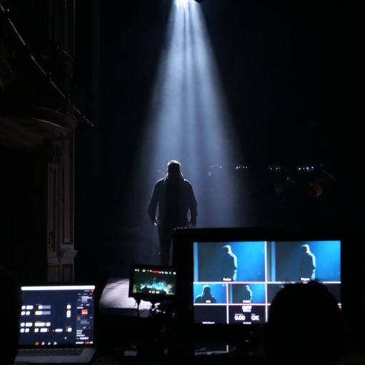 Na pierwszym planie monitory komputerów, za nimi - postać ludzka, która stoi na scenie, w półmroku.