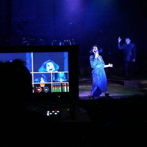 Na pierwszym planie monitor komputera, dalej - półmrok, aktorka w niebieskiej sukience stoi na scenie.