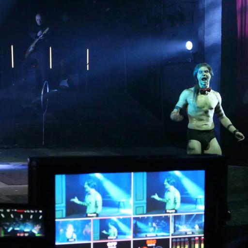 Na pierwszym planie monitor komputera, dalej - młody, umięśniony aktor z gołym torsem stoi na scenie.