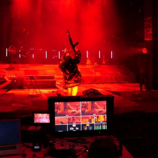 Na pierwszym planie monitor komputera, dalej -scena zanurzona w czerwonym świetle i męska sylwetka z uniesionym do góry karabinem maszynowym..