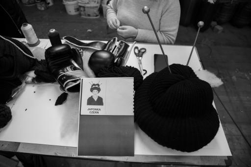 Na stoliku leżą materiały plastyczne, czarna peruka Chinki i kartka z projektem scenograficznym.