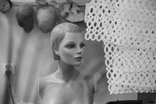 Na czarno-białej fotografii popiersie manekina-kobiety i fragment białej, ozdobnej siatki.