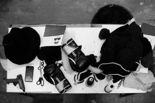 Czarno-biała fotografia. Na dużym stole rozłożonych jest kilkanaście niewielkich przedmiotów - nożyczki, materiały plastyczne, szpulki z nićmi, czarna peruka teatralna, rękawice bokserskie, telefon komórkowy.