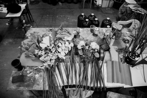 Na stole w pracowni plastycznej rozłożone są sztuczne kwiaty.