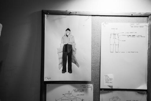 Fragment ściany, na której wisi rysunek - projekt kostiumu teatralnego.
