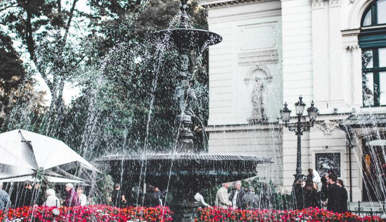 Na zdjęciu - ozdobna żeliwna fontanna przed budynkiem teatru, z której tryska woda.
