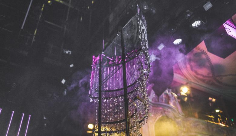 Uchwycone na zdjęciu od dołu reflektory sceniczne i kryształowy żyrandol zawieszony nad sceną.