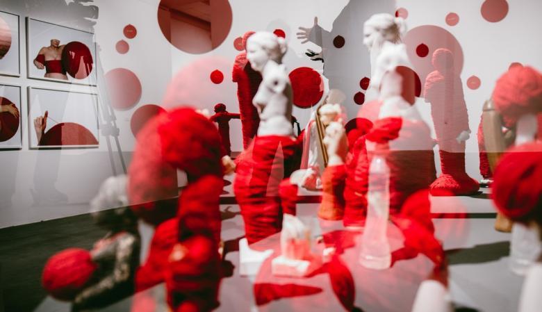 Na podeście ustawionych jest klika niewielkich białych figurek - postaci ludzkich owiniętych czerwoną włóczką.