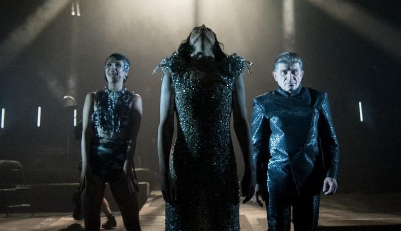 Trzy postacie - dwie kobiece i jedna męska - stoją w półmroku sceny.