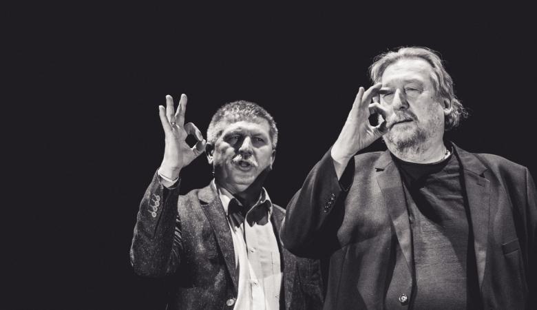 Dwóch mężczyzn pokazuje znaki języka migowego.