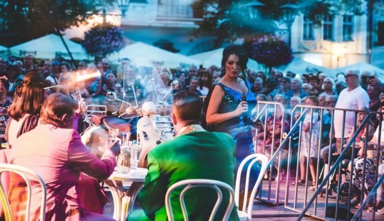na zdjęciu - wieczór, na rynku tłum ludzi w światłach reflektorów.