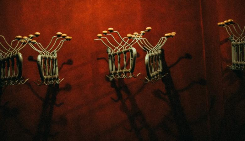 Kilka metalowych wieszaków w stylu retro na ciemnoczerwonej ścianie w teatralnej szatni.