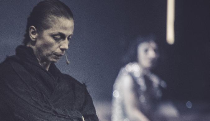 Kobieta w czarnym płaszczu stoi, lekko pochylona, ze spuszczonym wzrokiem i poważnym wyrazem twarzy. Na dalszym planie - niewyraźny zarys drugiej, ubranej w jasną suknię kobiety, która siedzi na schodach.