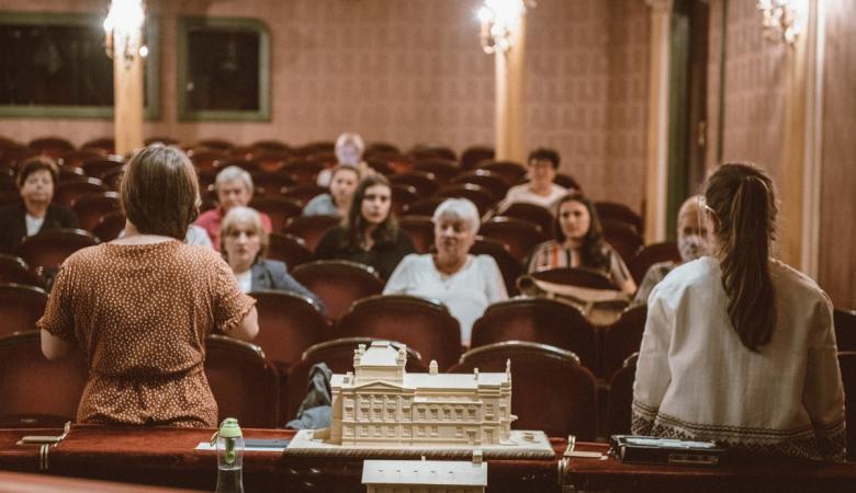 na brzegu sceny stoi makieta Teatru Polskiego, za nią widownia. Na bordowych fotelach siedzi kilka kobiet w różnym wieku.