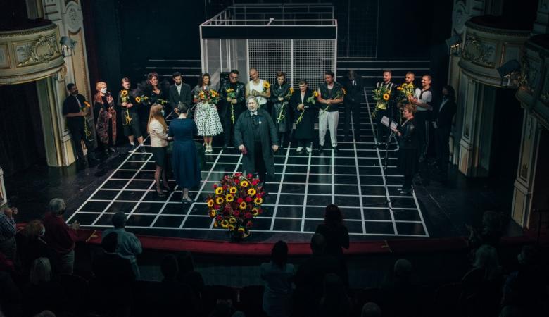 Aktorzy i aktorki stoją na scenie z bukietami kwiatów.